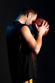 Zijaanzicht van de holdingsbal van de basketbalspeler aan zijn voorhoofd