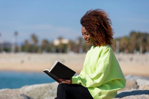 Zijaanzicht van de jonge krullende zitting van de afrovrouw op een golfbreker die een boek houden terwijl in openlucht het glimlachen en het lezen