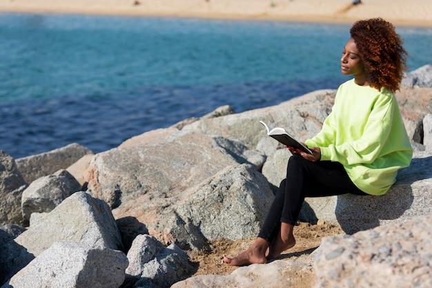 Zijaanzicht van de jonge krullende zitting van de afrovrouw op een golfbreker die een boek houden terwijl in openlucht het lezen