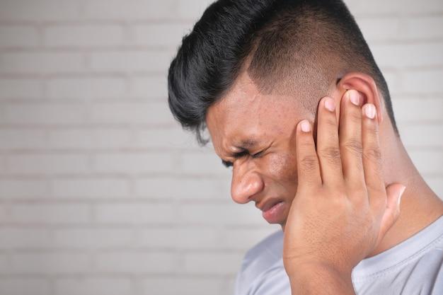 Zijaanzicht van de jonge man die pijn in het oor lijdt