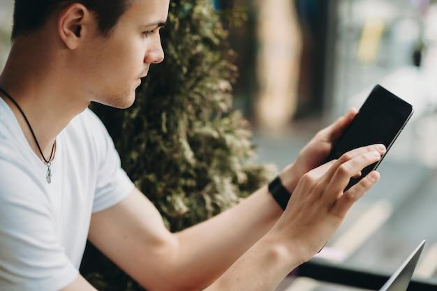 Zijaanzicht van de jonge man in casual outfit met behulp van tablet met leeg scherm zittend op onscherpe achtergrond van straat