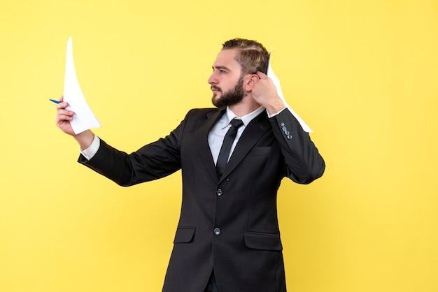 Zijaanzicht van de jonge man in zwart pak die over nieuw idee denkt terwijl hij blanco papier op de gele muur houdt