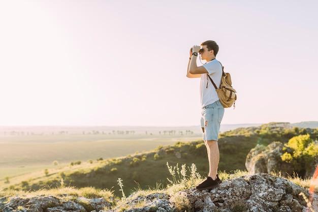 Zijaanzicht van de jonge mens die groen landschap onderzoekt door binoculair