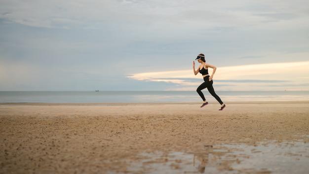 Zijaanzicht van de jonge vrouw in sportkleding joggen op het strand in de ochtend.