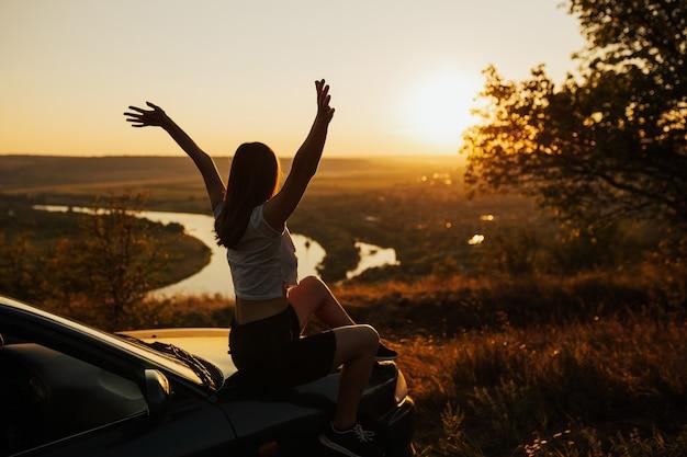 Zijaanzicht van de jonge vrouw reiziger met handen omhoog kijken naar prachtige zonsondergang zittend op de auto.