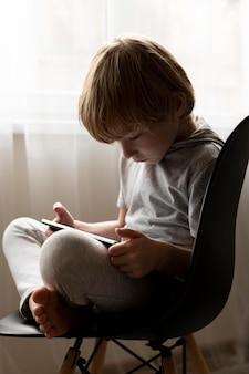 Zijaanzicht van de jongen die in klusje zit en tablet gebruikt