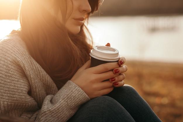 Zijaanzicht van de kalme jonge vrouw bijsnijden in warme gebreide trui genieten van warme afhaalkoffie zittend in de buurt van meer in zonnige herfstdag