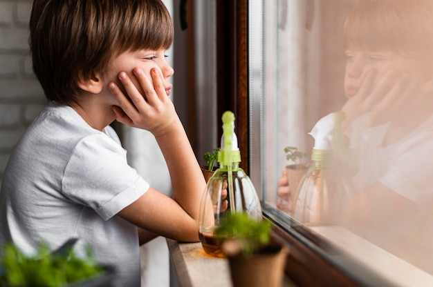 Zijaanzicht van de kleine jongen die door het raam met waternevel voor gewassen kijkt