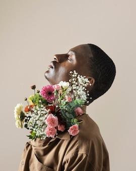 Zijaanzicht van de knappe man poseren met boeket bloemen