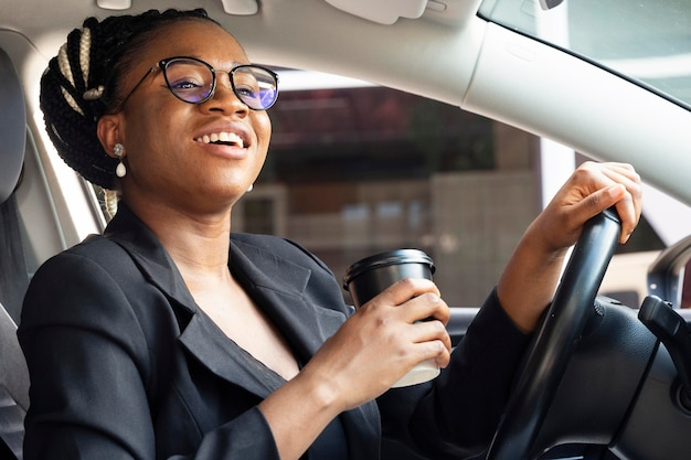 Zijaanzicht van de koffiekop van de vrouwenholding terwijl in haar auto