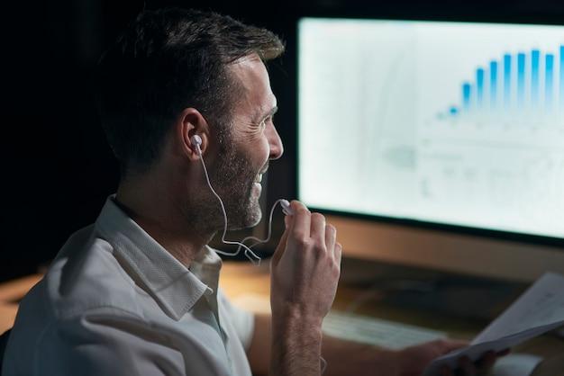 Zijaanzicht van de man die naar muziek luistert in zijn kantoor