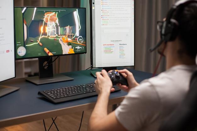 Zijaanzicht van de man met een koptelefoon tijdens het spelen van schietspellen op stream met behulp van een draadloze controller.