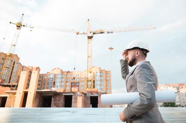 Zijaanzicht van de mannelijke bouwvakker van de ingenieursholding met blauwdruk die zich dichtbij bouwwerf bevinden