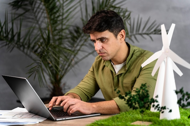 Zijaanzicht van de mens die aan een milieuvriendelijk windenergieproject met laptop werkt