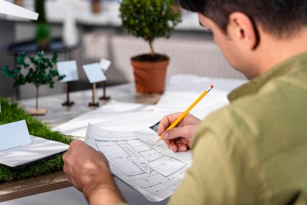 Zijaanzicht van de mens die aan een milieuvriendelijk windenergieproject werkt met papieren en potlood