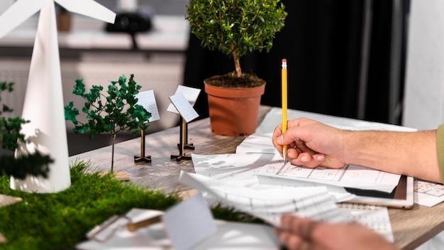 Zijaanzicht van de mens die aan een milieuvriendelijk windenergieproject werkt met papieren plannen