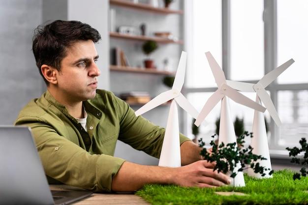 Zijaanzicht van de mens die aan een milieuvriendelijk windenergieproject werkt