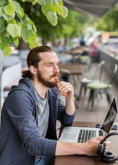 Zijaanzicht van de mens die aan laptop op een terras werkt