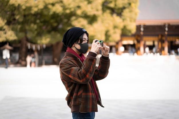 Zijaanzicht van de mens die buiten foto's neemt terwijl hij een gezichtsmasker draagt