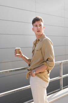 Zijaanzicht van de mens die buitenshuis poseren terwijl hij een kopje koffie vasthoudt