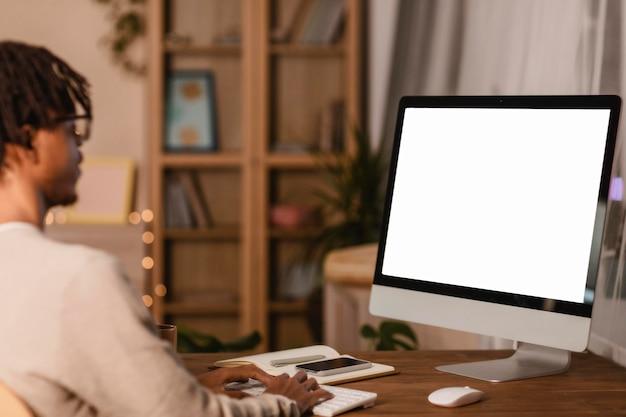 Zijaanzicht van de mens die computer thuis met behulp van