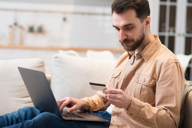 Zijaanzicht van de mens die creditcard voor online het winkelen bekijkt