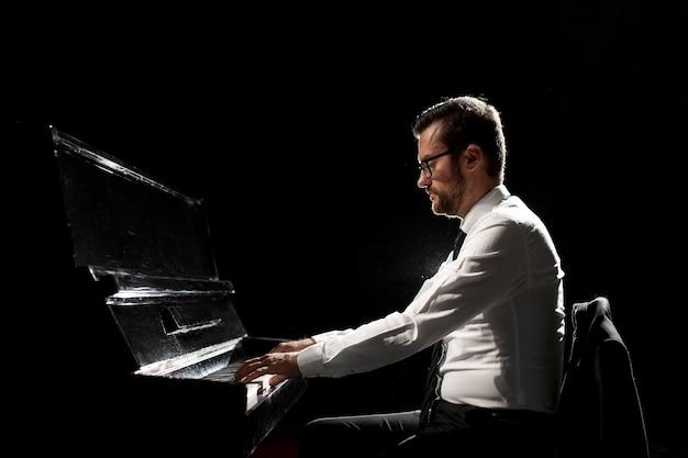 Zijaanzicht van de mens die de piano speelt