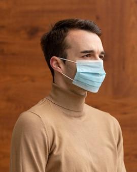 Zijaanzicht van de mens die een medisch masker draagt