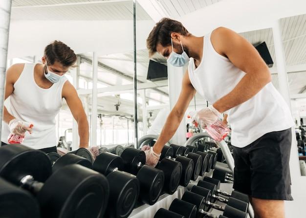 Zijaanzicht van de mens die fitnessapparatuur desinfecteert terwijl hij een medisch masker draagt