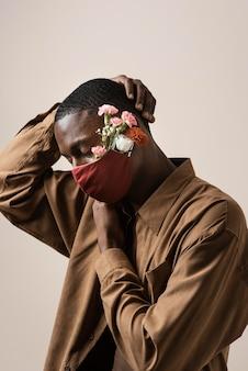 Zijaanzicht van de mens die gezichtsmasker en bloemen draagt