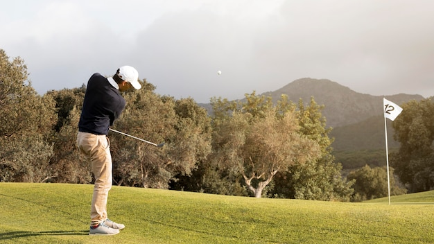 Zijaanzicht van de mens die golfbal op het gebied raakt