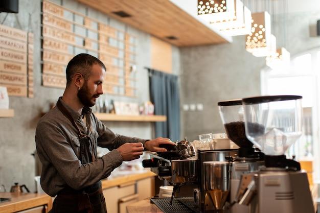 Zijaanzicht van de mens die in koffiewinkel werkt