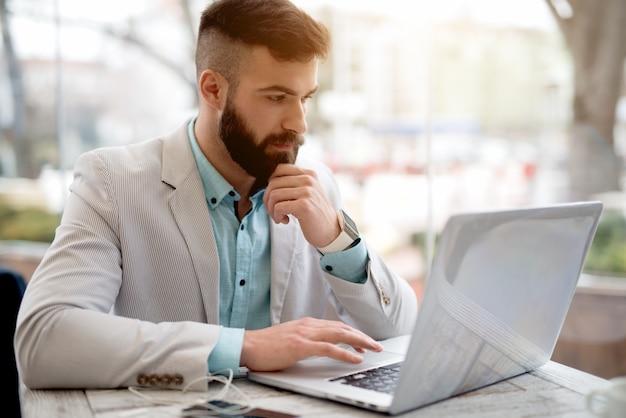 Zijaanzicht van de mens die in kostuum e-mails controleren op laptop