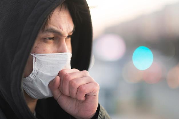 Zijaanzicht van de mens die in medisch masker hoest