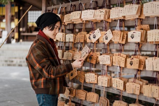 Zijaanzicht van de mens die japanse houten kaarten bekijkt