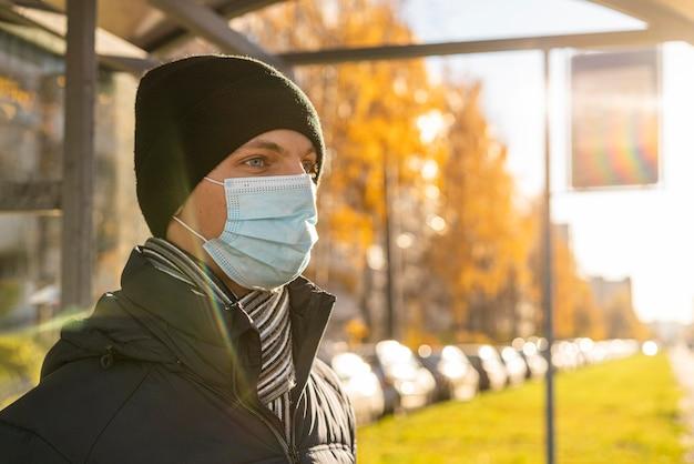 Zijaanzicht van de mens die met medisch masker op de bus wacht