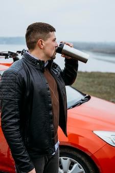 Zijaanzicht van de mens die naast auto drinkt