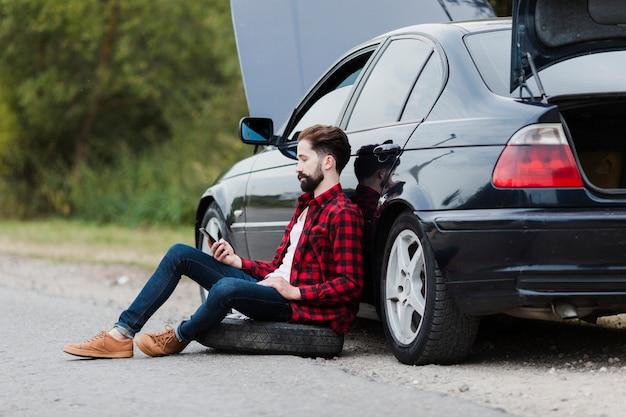 Zijaanzicht van de mens die op auto leunt