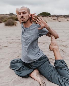 Zijaanzicht van de mens die op het strand yoga uitoefent