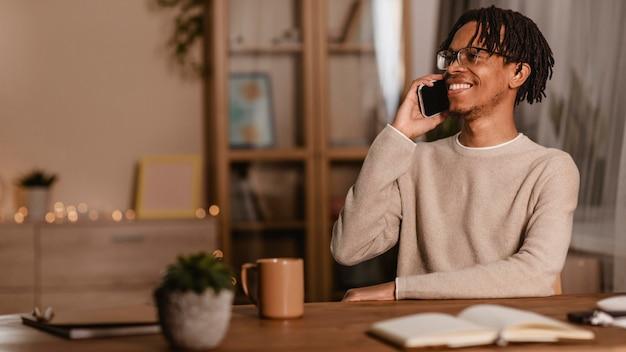 Zijaanzicht van de mens die op smartphone thuis spreekt