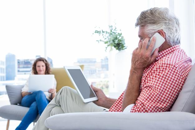 Zijaanzicht van de mens die op telefoon spreken terwijl thuis het houden van tablet