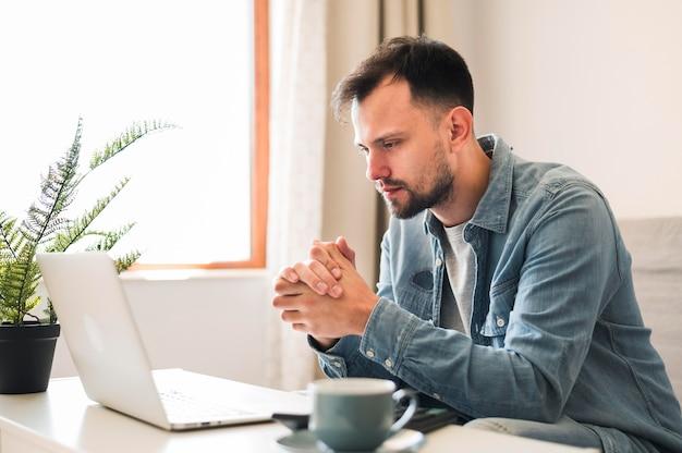Zijaanzicht van de mens die op zijn laptop wotking