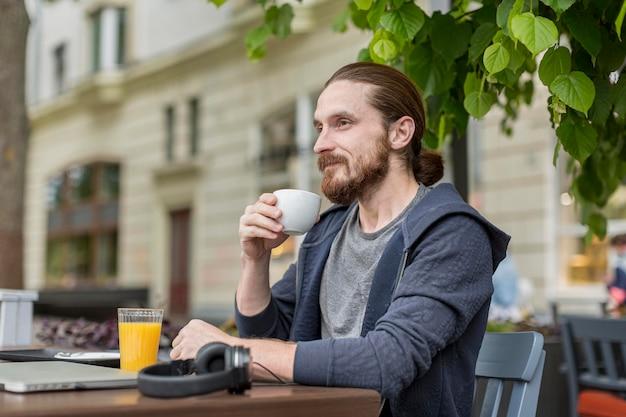 Zijaanzicht van de mens die van koffie geniet bij een stadsterras