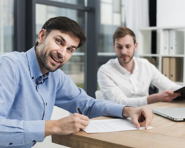 Zijaanzicht van de mens die werkcontract ondertekent