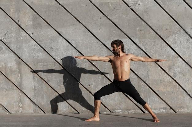 Zijaanzicht van de mens die yoga buiten doet