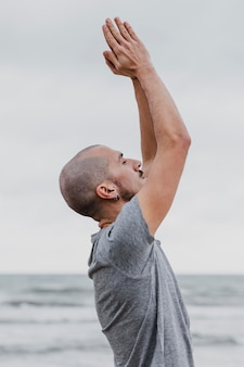 Zijaanzicht van de mens die yoga doet en zijn armen buitenshuis opheft