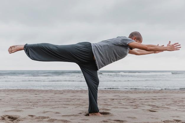 Zijaanzicht van de mens die yoga op het strand beoefent