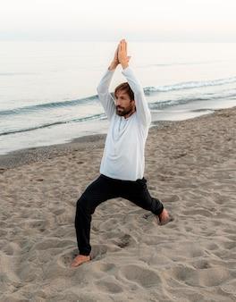 Zijaanzicht van de mens die yoga op het strand doet