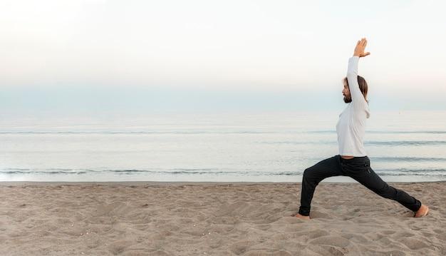 Zijaanzicht van de mens die yoga op het strand met exemplaarruimte doet