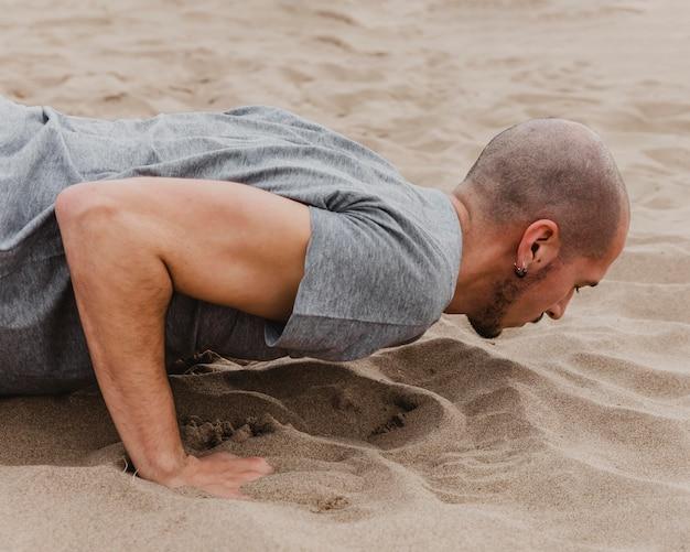 Zijaanzicht van de mens die yoga op zand doet